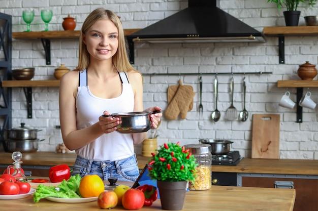 Vrouw in de keuken met een pot soep, thuis koken