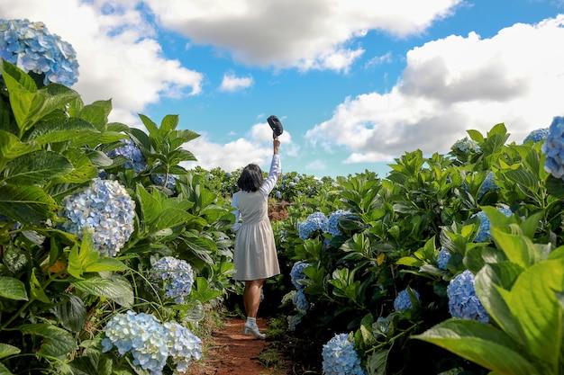 Vrouw in de kleurrijke tuin van de hydrangea hortensiabloem met blauwe hemel en wolkenachtergrond.