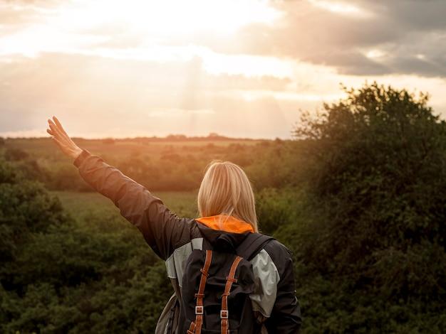 Vrouw in de natuur bij zonsondergang