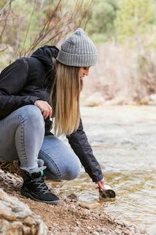 Vrouw in de natuur drinkwater uit de rivier