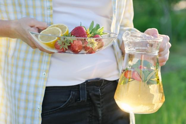 Vrouw in de natuur houden pot aardbeien munt en citroen