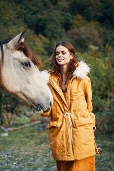 Vrouw in de natuur in een jas bij een ezel vriendschap dieren