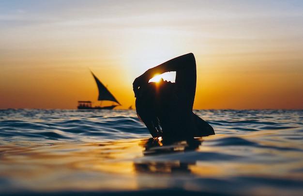 Vrouw in de oceaan in de zonsondergangtijd