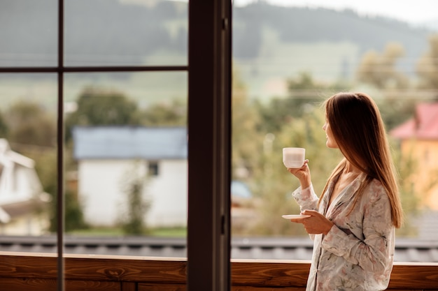 Vrouw in de ochtend die een kop thee of koffie houdt en de bergen bekijkt die zich dichtbij het venster bevinden