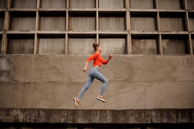 Vrouw in de oranje sweater en jeans die op de concrete bouw lopen