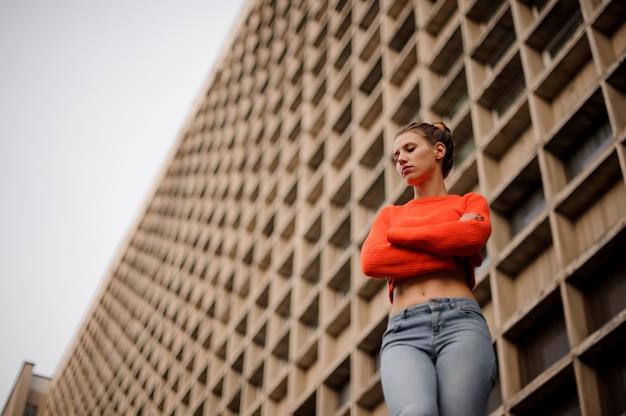Vrouw in de oranje sweater en jeans status. betonnen constructie