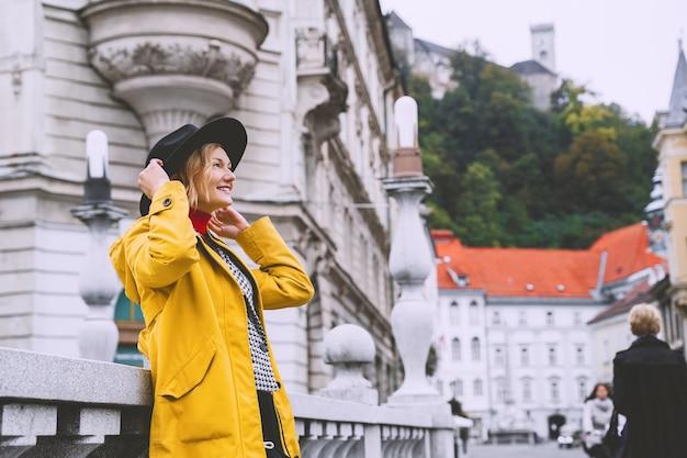 Vrouw in de oude binnenstad van ljubljana toerist op de achtergrond van stadsarchitectuur straatlook van stedelijk meisje