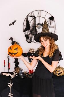 Vrouw in de pompoen van de heksenkostuum holding en het glimlachen
