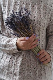 Vrouw in de roze gebreide trui met droge lavendelbloemen
