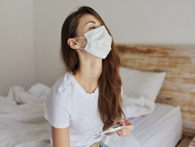 Vrouw in de slaapkamer met een medisch masker met een thermometer in haar handen