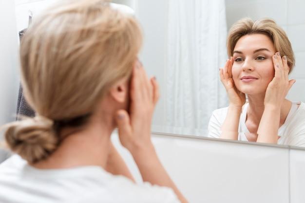 Vrouw in de spiegel kijken en glimlacht