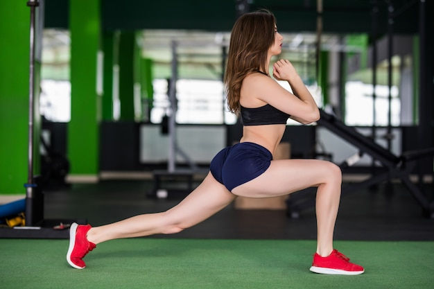 Vrouw in de sportschool doet verschillende oefeningen om haar lichaam sterker te maken