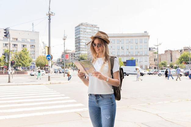 Vrouw in de stad die de kaart bekijkt