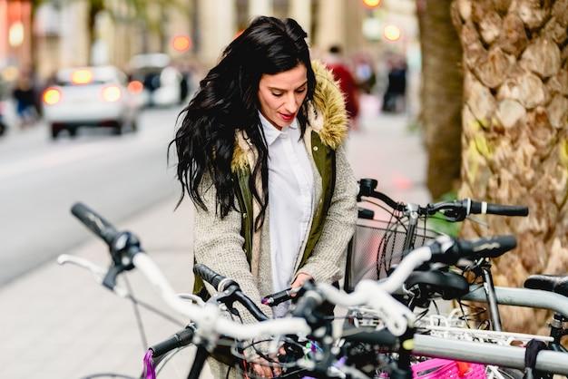 Vrouw in de stad met haar fiets stellende rust.