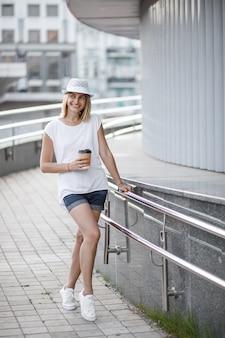 Vrouw in de stad met koffie, zomer en zonnig weer.