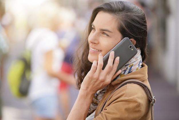 Vrouw in de straat die op telefoon spreekt
