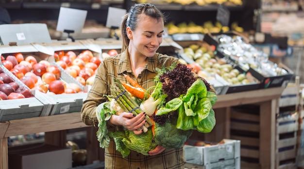 Vrouw in de supermarkt. mooie jonge vrouw die in een supermarkt winkelt en verse biologische groenten koopt