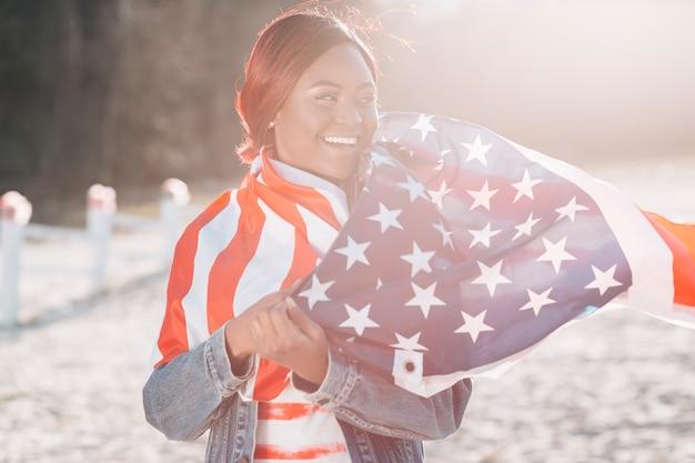 Vrouw in de vlag die van de vs wordt verpakt die zich op zand bevindt