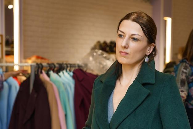 Vrouw in de winkel die een jas koopt