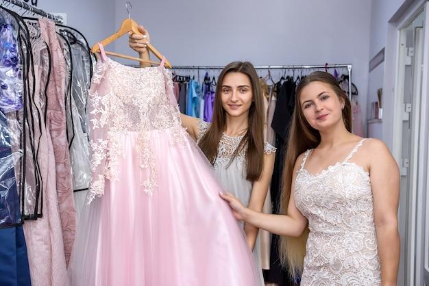 Vrouw in de winkel die nadenkt over het kopen van een nieuwe jurk