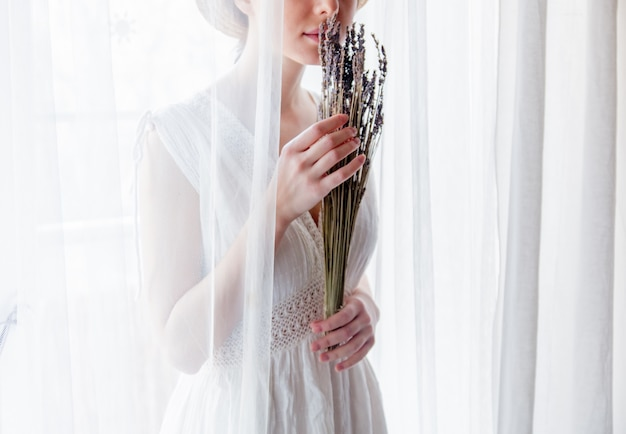 Vrouw in de witte lavendel van de kledingsholding dichtbij venster