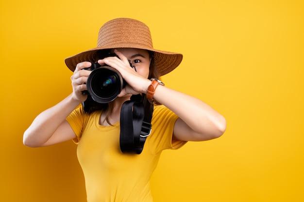 Vrouw in de zomerhoed die zich met fotocamera bevindt die over gele achtergrond wordt geïsoleerd