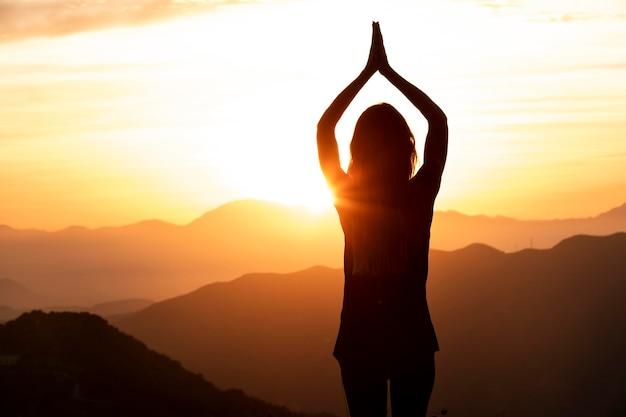 Vrouw in de zonsondergang die yoga doet