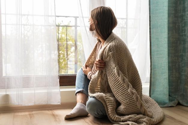 Vrouw in deken met medisch masker die door het raam kijken tijdens de pandemie