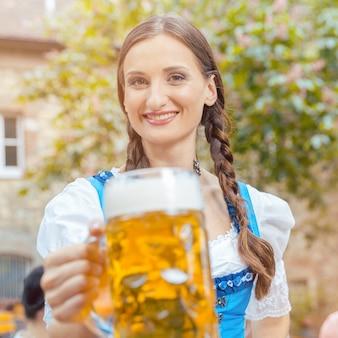 Vrouw in dirndl-jurk drinkt bier in een beierse biertuin