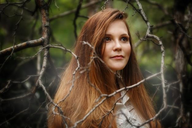 Vrouw in donker bos, wegkijken