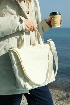 Vrouw in donsjack met papieren beker en stijlvolle eco-tas tegen zee