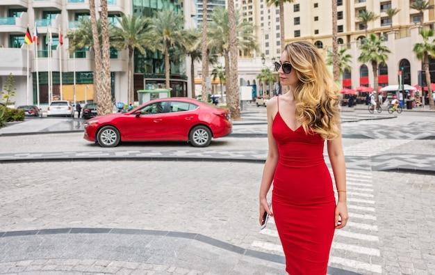 Vrouw in dubai, verenigde arabische emiraten. aantrekkelijke dame draagt een rode jurk. meisje dat de stadsmeningen bewondert