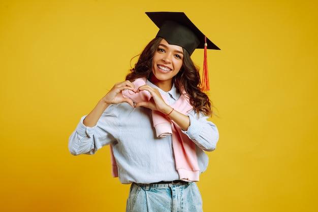 Vrouw in een afstuderen hoed liefde teken doet