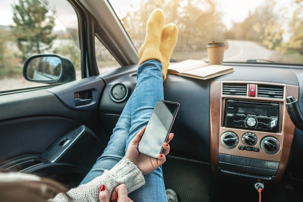 Vrouw in een auto in warme sokken houdt een gsm-gadget en een kopje koffie vast