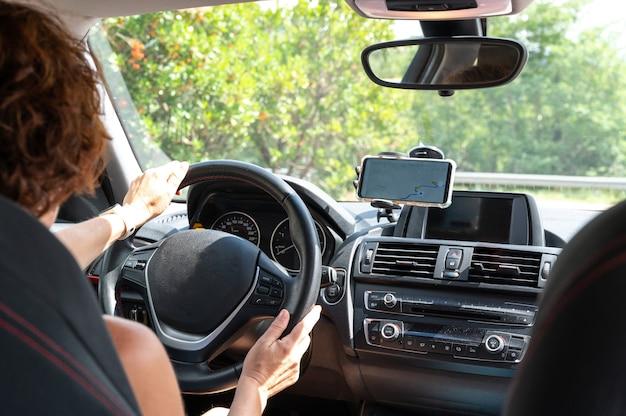 Vrouw in een auto, rijdt volgens de aanwijzingen van een gps