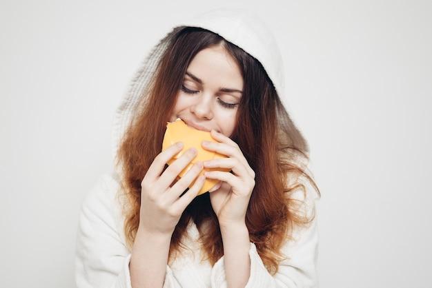 Vrouw in een badjas die thuis een boterham eet
