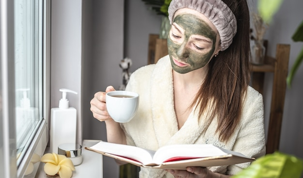 Vrouw in een badjas en met een groen cosmetisch masker op haar gezicht leest een boek en drinkt thee