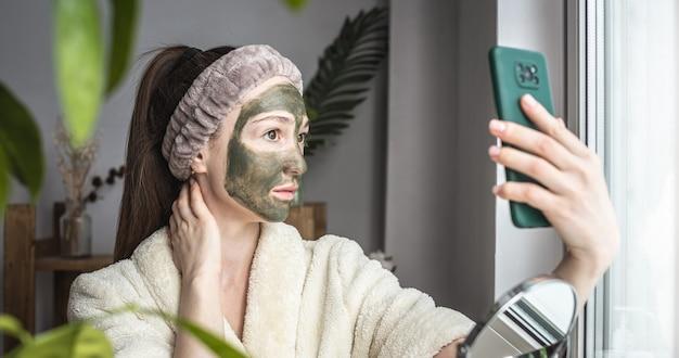 Vrouw in een badjas en met een groen cosmetisch masker op haar gezicht maakt een selfie op haar mobiele telefoon
