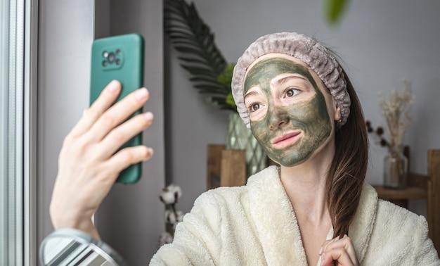 Vrouw in een badjas en met een groen cosmetisch masker op haar gezicht maakt een selfie op haar telefoon