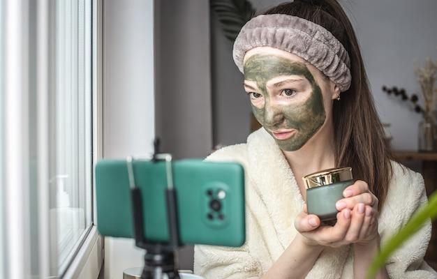 Vrouw in een badjas met een groen cosmetisch masker op haar gezicht toont een pot masker op een mobiele telefoon