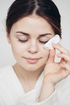 Vrouw in een badjas veegt haar gezicht af met een zachte spons schone huid cosmetologie. hoge kwaliteit foto