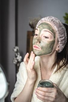 Vrouw in een badjas voor een spiegel brengt een groen cosmetisch masker op haar gezicht aan