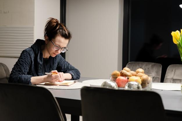 Vrouw in een badjas zit 's nachts aan een tafel en schrijft in een notitieblok