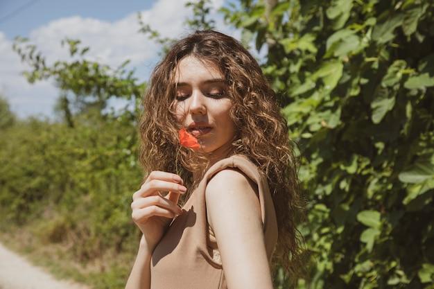 Vrouw in een beige jurk ruiken een poppy bloem