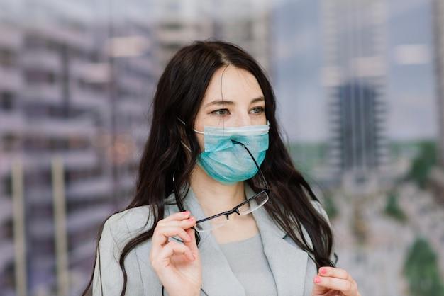 Vrouw in een beschermend gezichtsmasker op openbare plaats. coronavirus, covid-19 verspreid preventieconcept, verantwoord sociaal gedrag van een burger