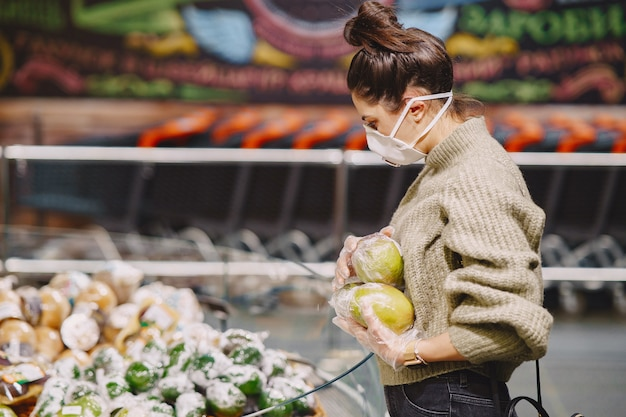 Vrouw in een beschermend masker in een supermarkt