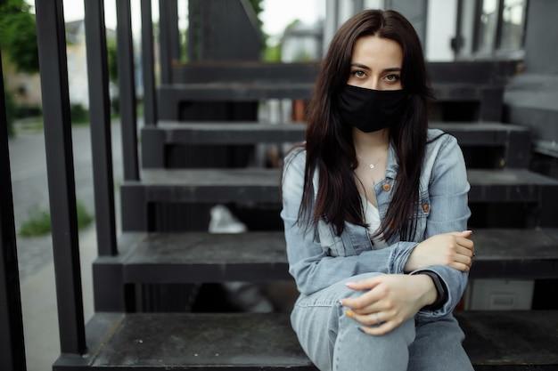 Vrouw in een beschermend masker op een balkon kijkt naar een lege stad