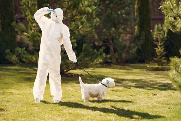 Vrouw in een beschermend pak wandelen met een hond