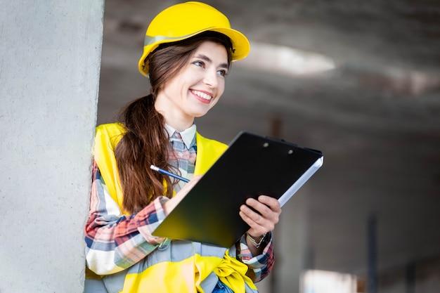 Vrouw in een beschermende helm en een reflecterend vest voert een inspectie uit op een bouwplaats