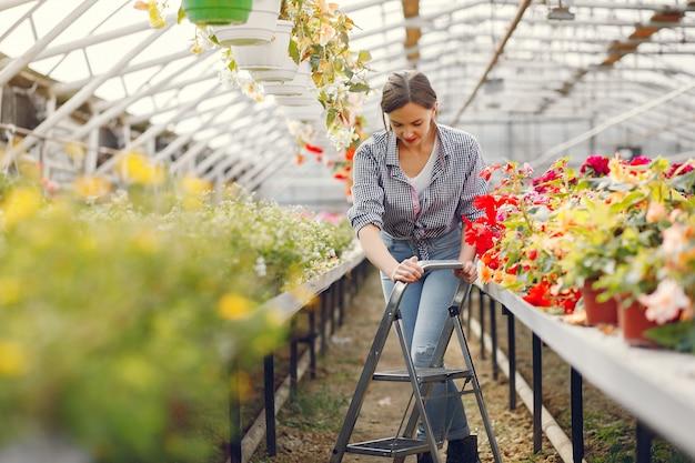 Vrouw in een blauw shirt dat in een serre werkt